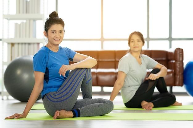 Junge attraktive lächelnde frau, die yoga praktiziert, sportbekleidung tragend, ruhe und entspannung, weibliches glück.