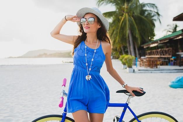Junge attraktive lächelnde frau im blauen kleid, das auf tropischem strand mit fahrradhut und sonnenbrille geht