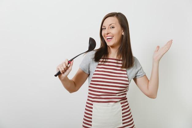Junge attraktive lächelnde kaukasische hausfrau in der gestreiften schürze lokalisiert. schöne haushälterin singt in die küchensuppe wie ein mikrofon kitchen