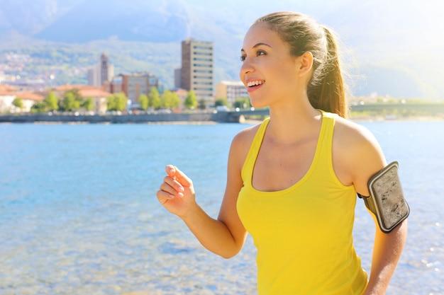 Junge attraktive läuferfrau der fitness mit armband für telefontraining durch den stadtsee. speicherplatz kopieren.
