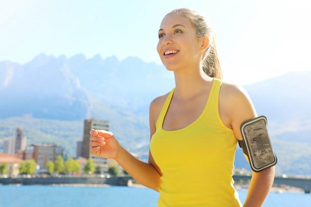 Junge attraktive läuferfrau der fitness mit armband für telefontraining durch den stadtsee.