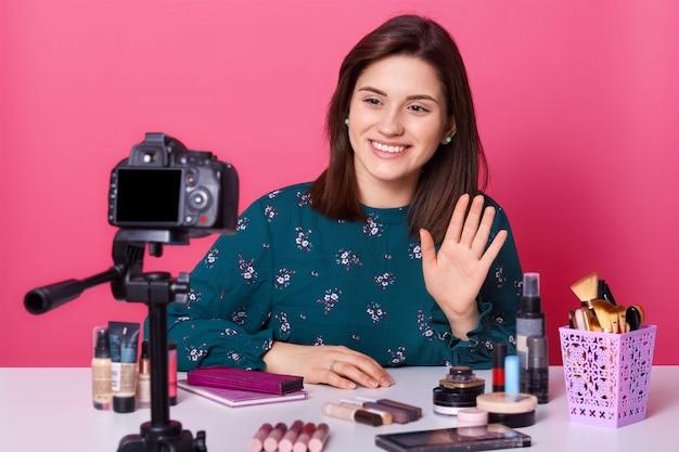 Junge attraktive lebhafte bloggerin erhebt ihre hand, begrüßt ihre zuschauer, nimmt videos für den kanal auf und macht ein tutorial über make-up