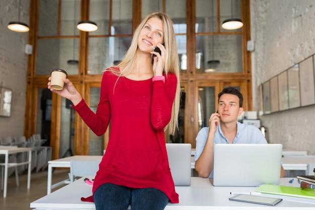 Junge attraktive leute, die online im offenen büroraum zusammenarbeiten,