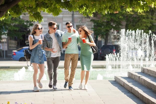Junge attraktive leute, die spaß zusammen draußen haben. leute, die kaffee trinken und lächeln. gruppe von freunden zusammen spazieren.