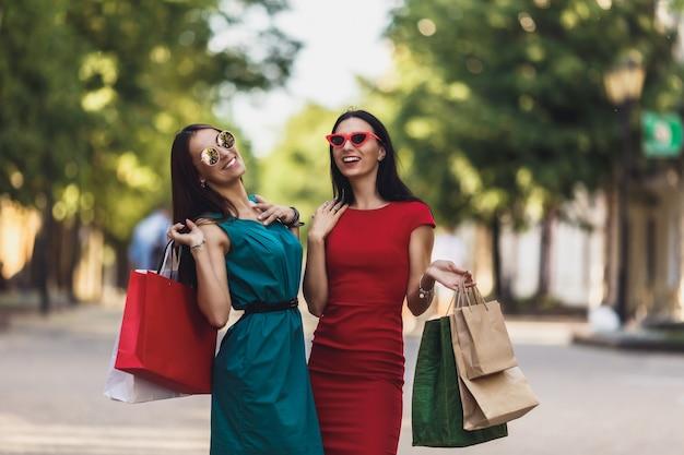Junge attraktive mädchen mit einkaufstaschen in der sommerstadt.