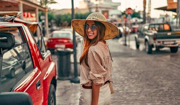 Junge attraktive mädchentouristin in einer bluse, einem strohhut und einer sonnenbrille, die durch die straßen der stadt durch ein rotes auto geht. das konzept des tourismus, reisen.