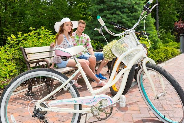 Junge attraktive männer und frauen, die einen weißen hut tragen, sitzen auf einer bank in der nähe von fahrrädern, die auf einem ziegelsteingehweg in einem schönen grünen park geparkt sind