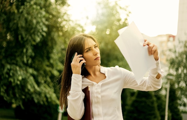 Junge attraktive managerin hält papierblätter, die draußen in der stadt telefonieren. alles im geschäft