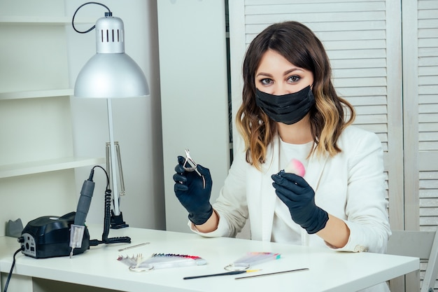Junge attraktive maniküre-profi (maniküre-meisterin) in weißer jacke, maske und schwarzen gummihandschuhen wählt nagellack in einem beauty-spa-salon am arbeitsplatz.