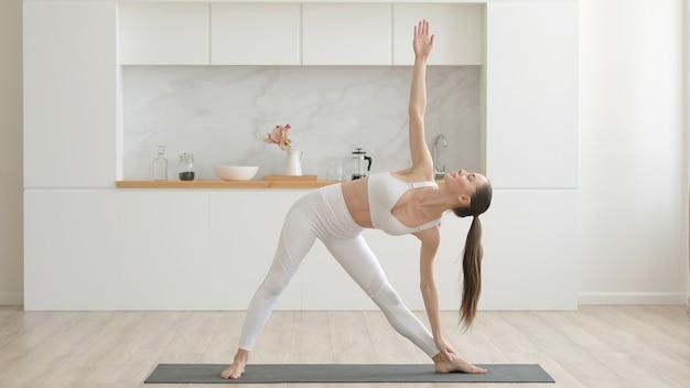 Junge attraktive multiethnische frau mit weißen sporthosen und top, die stretching-yoga-übungen auf der fitnessmatte im gesundheitswesen im wohnzimmer und mentale therapie zu hause macht