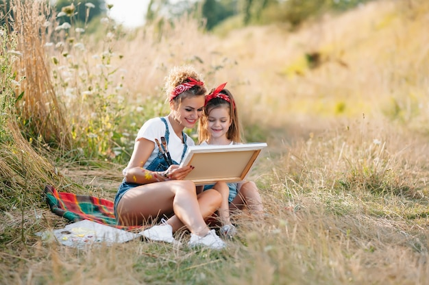 Junge attraktive mutter unterrichtet tochtermalerei im sommerpark. aktivität im freien für kinder im schulalter