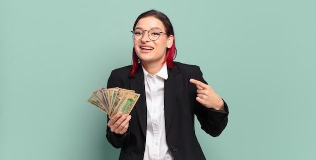 Junge attraktive rote haarfrau, die aufgeregt und überrascht schaut und zur seite und nach oben zeigt, um raum zu kopieren. geldkonzept