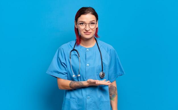 Junge attraktive rote haarfrau, die fröhlich lächelt, sich glücklich fühlt und ein konzept im kopienraum mit handfläche zeigt. krankenhauskrankenschwester-konzept