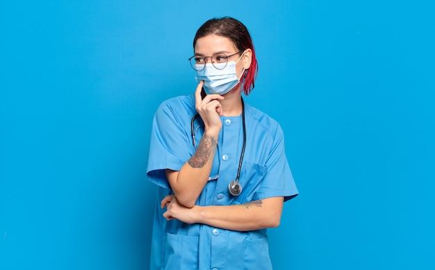 Junge attraktive rote haarfrau, die mit einem glücklichen, selbstbewussten ausdruck mit der hand am kinn lächelt, sich wundert und zur seite schaut. krankenhauskrankenschwester-konzept