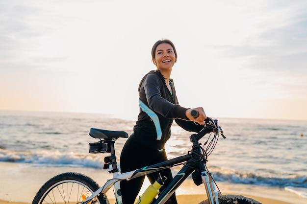Junge attraktive schlanke frau, die fahrrad reitet, sport im morgensonnenaufgang-sommerstrand in sportfitnesskleidung, aktiver gesunder lebensstil, lächelnd glücklich, spaß zu haben