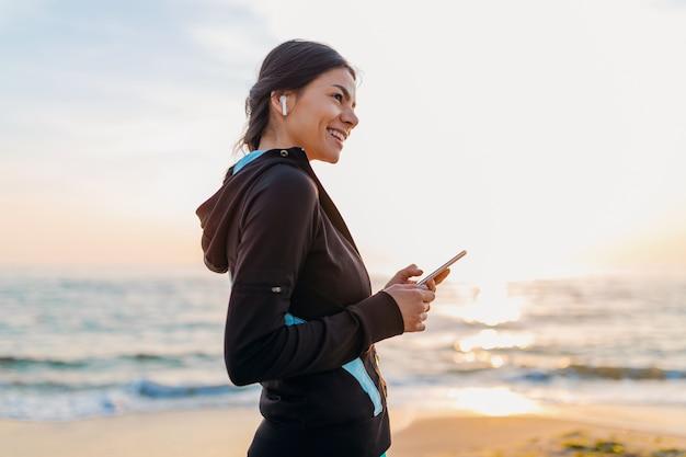 Junge attraktive schlanke frau, die sportübungen am morgensonnenaufgangstrand in der sportkleidung, im gesunden lebensstil, im musikhören auf drahtlosen kopfhörern hält, die smartphone halten, glücklich lächelnd spaß haben