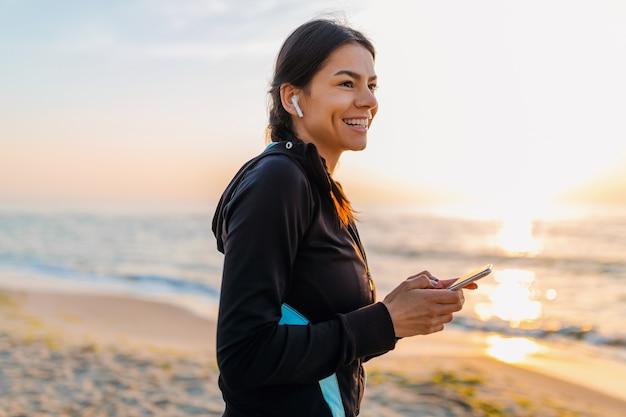 Junge attraktive schlanke frau, die sportübungen am morgensonnenaufgangstrand in der sportkleidung, im gesunden lebensstil tut, musik auf drahtlosen kopfhörern haltend smartphone hält und glücklich lächelt