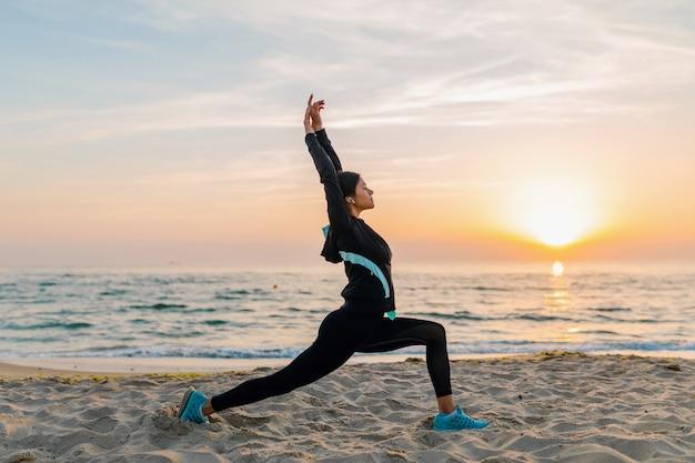 Junge attraktive schlanke frau, die sportübungen am morgensonnenaufgangstrand in sportkleidung, gesundem lebensstil, musik auf kopfhörern hörend macht, das strecken macht