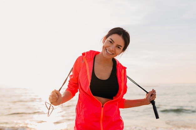 Junge attraktive schlanke frau, die sportübungen im morgensonnenaufgang am meeresstrand in der sportkleidung, im gesunden lebensstil, trägt rosa windbreakerjacke tut, springseil hält