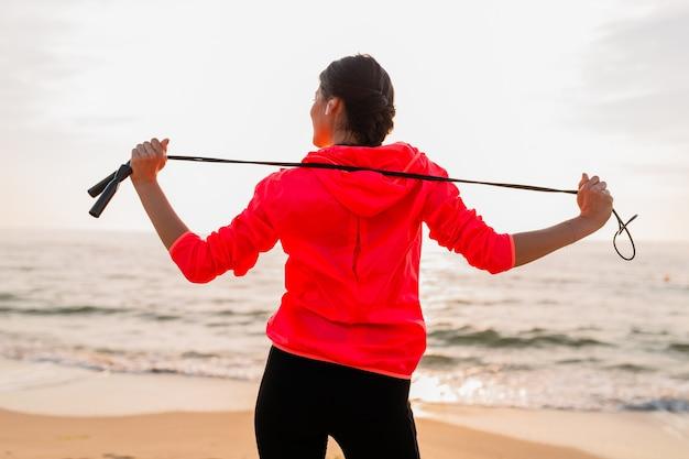 Junge attraktive schlanke frau, die sportübungen im morgensonnenaufgang am meeresstrand in sportbekleidung, gesundem lebensstil, musik auf kopfhörern hörend, rosa windbreakerjacke tragend, springseil haltend macht