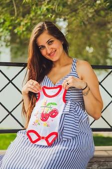Junge attraktive schwangere frau. schwangere frau, die einen babykörper hält. stadt lifestyle-konzept.