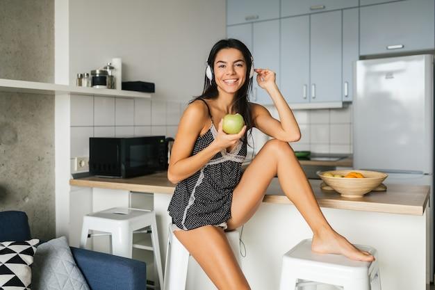 Junge attraktive sexy frau, die frühstück in der küche am morgen, apfel aß, lächelnd, glücklich, positiv, gesunder lebensstil, musik auf kopfhörern hörend