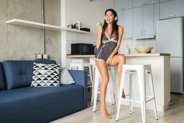 Junge attraktive sexy frau, die frühstück in der stilvollen modernen küche am morgen isst, apfel isst, lächelt, glücklich, positiv, gesunder lebensstil, musik auf kopfhörern hört, lacht, spaß hat