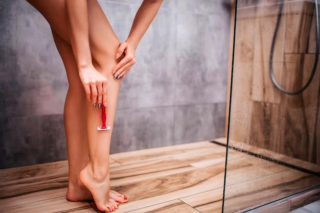 Junge attraktive sexy frau in der dusche. nackter körper. sie rasiert sich die beine mit einem scharfen rasiermesser. posieren. gut gebaut und sportlich. trockenrasur. schnittansicht.