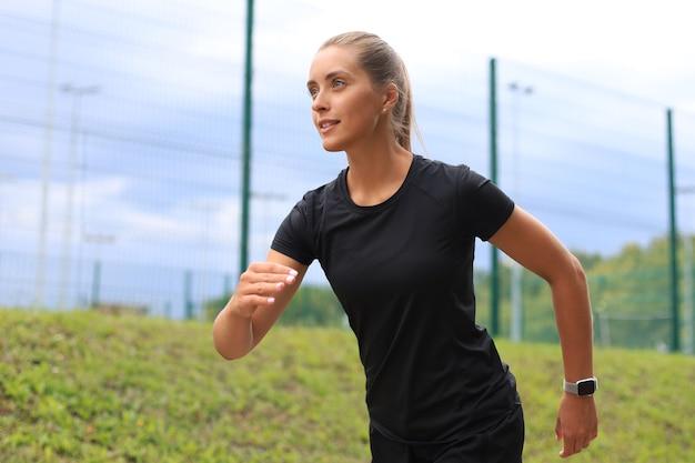 Junge attraktive sportliche fitnessfrau, die bei sonnenuntergang oder sonnenaufgang im freien trainiert.