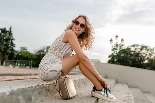 Junge attraktive stilvolle blonde frau, die in der stadtstraße im sommermodeartkleid sitzt, das sonnenbrille, geldbörse, silberne turnschuhe trägt