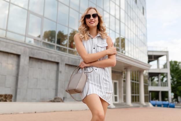 Junge attraktive stilvolle frau mit der blonden lockigen frisur, die in der stadtstraße im weißen gestreiften kleid der sommermodeart trägt, die sonnenbrille hält, die geldbörse hält