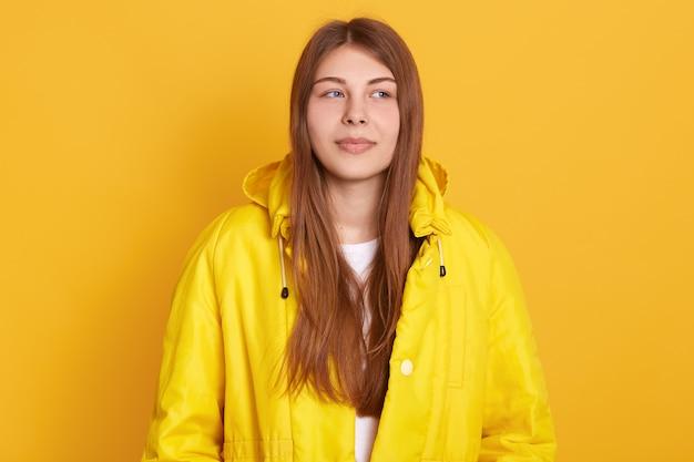Junge attraktive studentin, die jacke trägt, schönes glattes haar hat, das gegen gelbe wand steht, sieht nachdenklich aus.