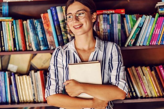 Junge attraktive studentin im kleid, die in der bibliothek vor regalen mit büchern steht und ihren lieblingsroman hält.