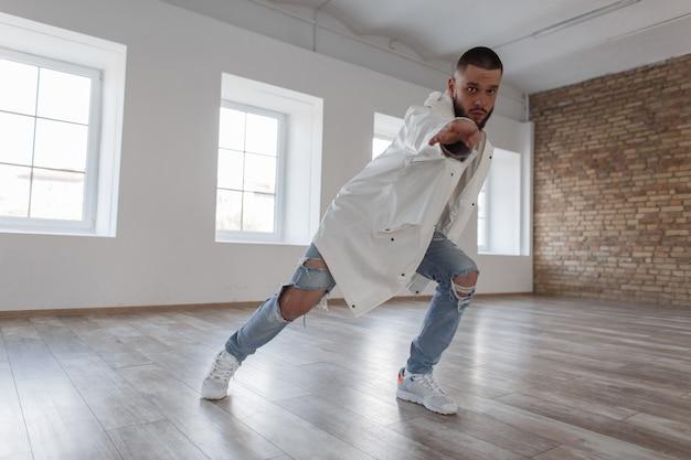 Junge attraktive tänzerin in trendiger jacke und zerrissenen jeans, die in der tanzhalle tanzen