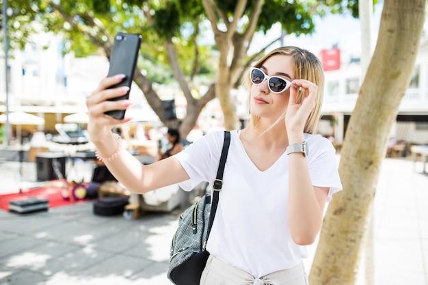 Junge attraktive verspielte touristenfrau macht selfie am telefon draußen