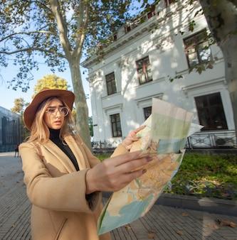 Junge attraktive weibliche reisende wird vom stadtplan geführt. schönes mädchen, das richtung in der stadt sucht. urlaubs- und tourismuskonzept