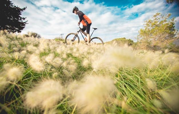 Junge auf dem mountainbike, das durch wiese radelt