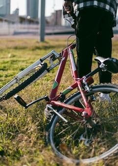 Junge auf dem rasen hält sein fahrrad