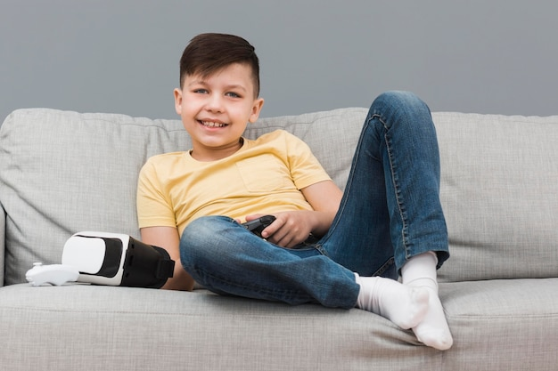 Junge auf dem sofa, der videospiele spielt