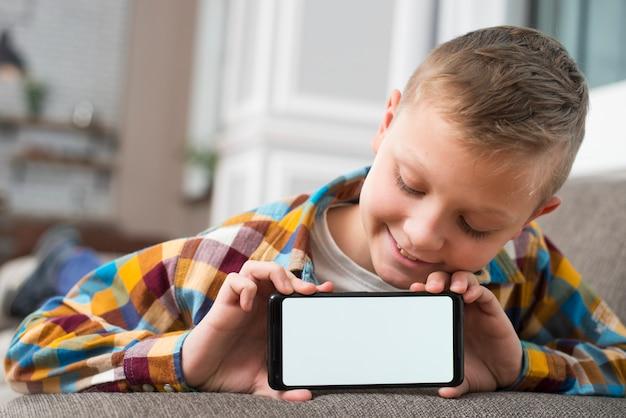 Junge auf der couch, die smartphoneschirm zeigt