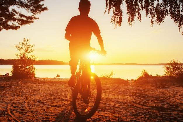 Junge auf einem fahrrad bei sonnenuntergang