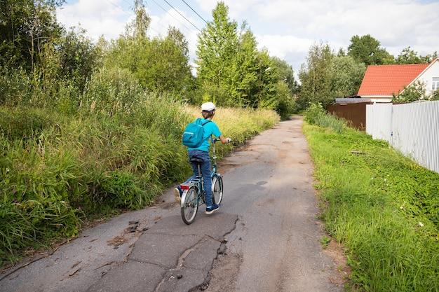 Junge auf fahrrad auf dorfstraße mit grünen bäumen von hinten