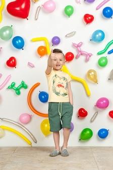 Junge auf weißem hintergrund mit bunten luftballons junge hebt seine hände auf weißem hintergrund