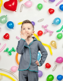 Junge auf weißem hintergrund mit bunten luftballons junge sendet einen luftkuss auf weißem hintergrund