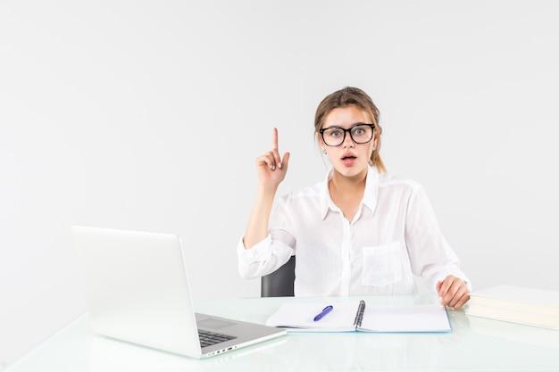 Junge aufgeregte frau in den pastellkleidern, die zeigefinger mit großer neuer idee halten, sitzen, arbeiten am schreibtisch mit laptop lokalisiert auf grauem hintergrund. erfolgsgeschäft karrierekonzept.