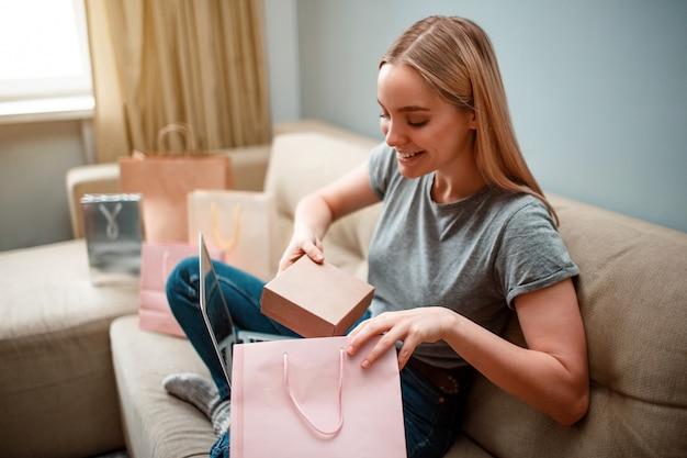 Junge aufgeregte frau packt ihr paket aus, das über das internet bestellt wird, während sie auf dem sofa sitzt