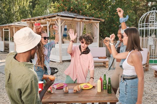 Junge aufgeregte freunde tanzen und amüsieren sich auf einer party im freien