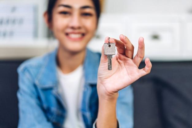 Junge aufgeregte, glückliche asiatische frau, die einen neuen hausschlüssel in den händen hält und ein neues zuhause kauft und umzieht. geschäfts- und immobilienkonzept