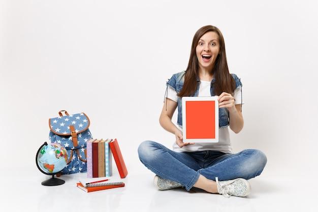 Junge aufgeregte studentin mit tablet-pc-computer mit leerem schwarzen leeren bildschirm, der in der nähe von globus-rucksack-schulbüchern sitzt