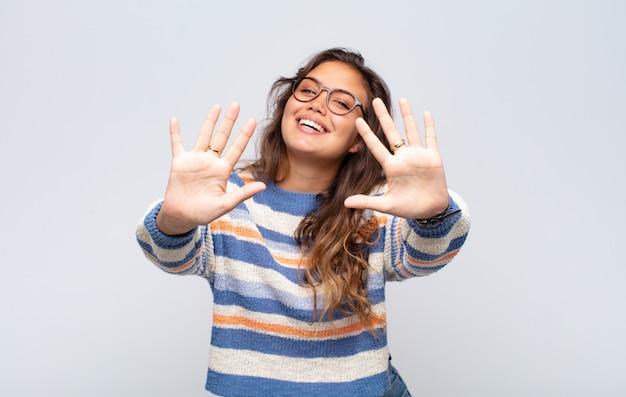 Junge ausdrucksstarke frau mit brille posiert auf weißer wand